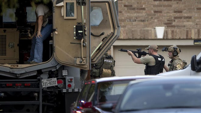 Law enforcement officers work in front of a house on Natalie Cove in the Heritage Park subdivision in Cedar Park where a standoff that started Sunday afternoon and ended the next morning left three officers injured. The suspect, 26-year-old Joseph Desean Taylor, surrendered Monday.