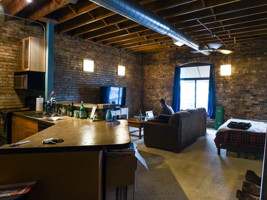 Alec Faggion works at home in his loft space in the 600 block of East Michigan Avenue, Friday, May 11, 2018.  Faggion is a recent MSU graduate, who likes living downtown, where he is close to his job at the State Capitol, restaurants, and local businesses.