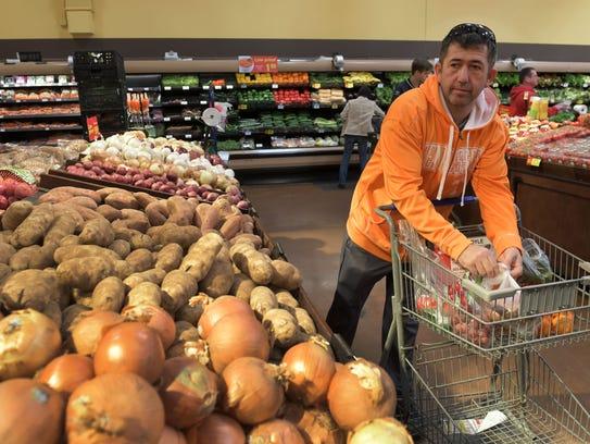 Tahir Kelleci shopping in the produce department at