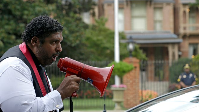 Rev. William Barber, president of the North Carolina branch of the NAACP, speaks to protesters as they march around the executive mansion to demonstrate against voting law changes by the state's Republican-led legislature.