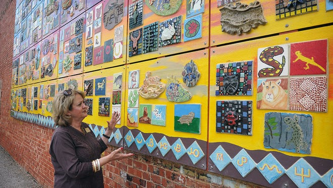 The Arts for All Community Mural on the Zales building will be dedicated during the Art & Soul Festival downtown June 24. Francine Carraro, director of the Wichita Falls Museum of Art at Midwestern State University, looks over the mural after its installation a few weeks ago.