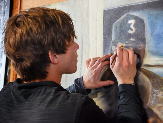Artist Jordan Weisenauer paints in a barn next to the