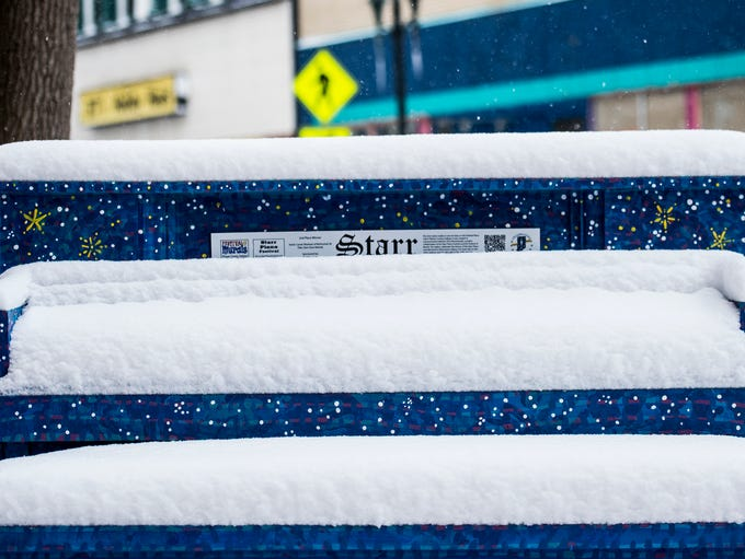 A Starr piano covered in snow sits along the sidewalk