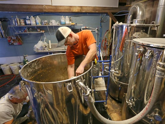 Head brewer Ian Conboy, right, and Mike Ward work on