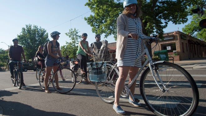 Cyclists line up to cross the intersection of Oak and Mason Streets during Bike to Work Day on Wednesday, June 27, 2018.