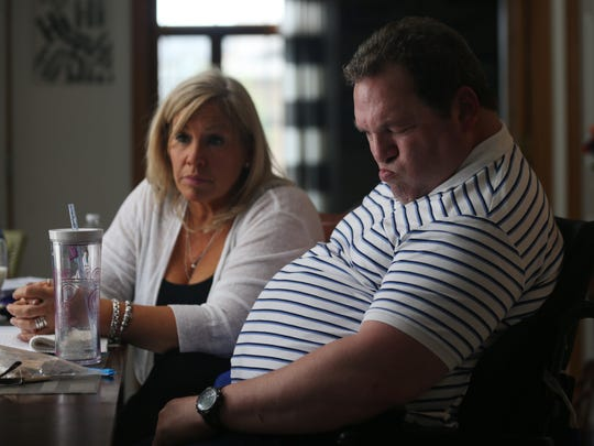 Neal Siegel and his girlfriend, Beth Wargo sit at their kitchen table on Thursday, June 8, 2017, at their home in West Des Moines. A bike accident a few years ago left Siegel with a brain injury.
