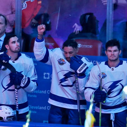 Tampa Bay Lightning right wing J.T. Brown, center, raises his fist in the air during the singing of the national nnthem before the start of an NHL hockey game between the Florida Panthers and the Tampa Bay Lightning, Saturday, Oct. 7, 2017, in Sunrise, Fla. (AP Photo/Wilfredo Lee), ORG XMIT: FLWL101