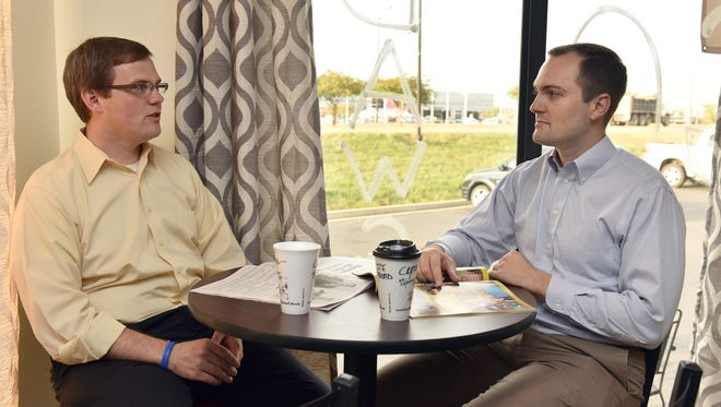 Brothers Kyle (left) and Ryan Brown of Brandon, who are on opposite sides of the political spectrum, talk at  a coffee shop in  Brandon.
