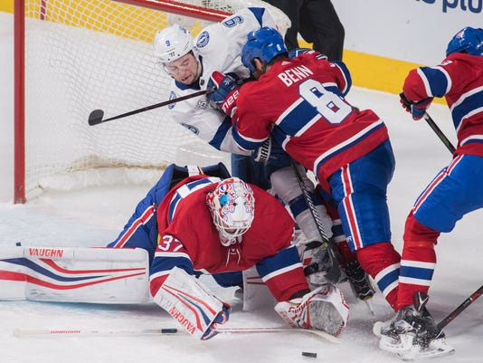 Tampa Bay Lightning center Tyler Johnson (9) moves in against Montreal Canadiens goaltender Antti Niemi (37) as defensemen Jordie Benn (8) and Noah Juulsen (58) defend during first-period NHL hockey game action in Montreal, Saturday, Feb. 24, 2018. (Graham Hughes/The Canadian Press via AP)