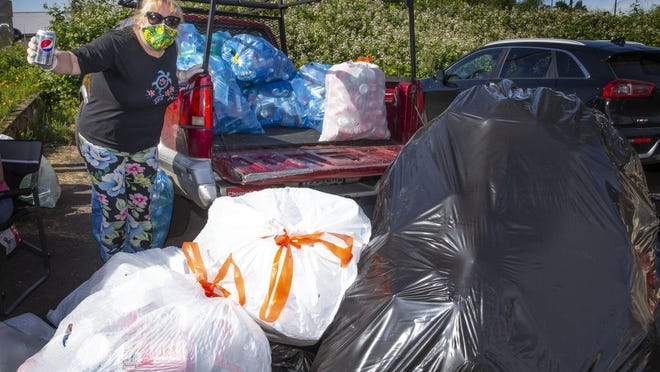"""Alisa Kounovsky stands behind bags of cans collected on her first day collecting for We """"CAN"""" Help project to help connect seniors with restaurants for a free meal. [Chris Pietsch/The Register-Guard] - registerguard.com"""