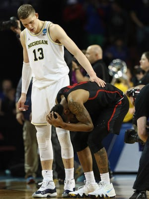 Moritz Wagner of the Michigan Wolverines tries to console Devin Davis, Corey Davis' teammate on the Houston Cougars, after Saturday night's game.