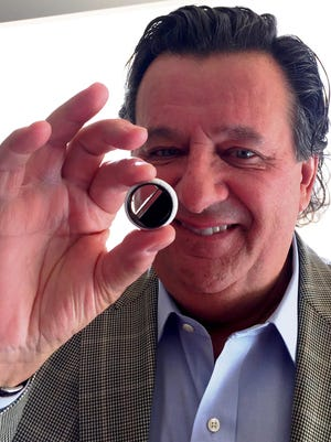 Dr. Roberto Amado-Cattaneo, a cardiothoracic surgeon at Benefis Health System, holds up one of the artificial heart valves he is taking with him when he and a team of health care specialists head to Ethiopia to perform surgeries on patients with rheumatic heart disease.