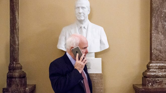 Senate Armed Services Committee Chairman Sen. John McCain, R-Ariz  makes a phone call beneath a bust of former Vice President Spiro Agnew just off the Senate floor, Tuesday, Jan. 13, 2015, on Capitol Hill in Washington.