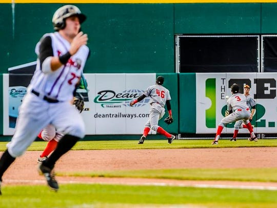 Connor Panas ,left, of the Lugnuts speeds toward home as Brendon Davis ,3, of the Loons moves to control a hit by Jake Thomas of the Lugnuts in the bottom of the 5th inning of their game Wednesday June 15, 2016 at Cooley Law School Stadium in Lansing.