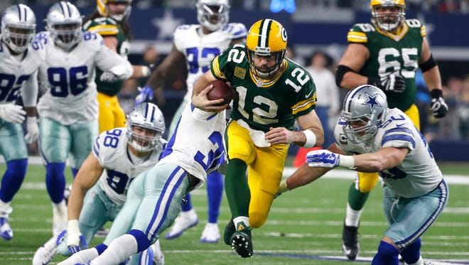 Green Bay Packers quarterback Aaron Rodgers (12) rushes for a gain as Dallas Cowboys' Sean Lee (50) and Anthony Brown (30) defend during the second half of an NFL divisional playoff football game Sunday, Jan. 15, 2017, in Arlington, Texas. (AP Photo/Michael Ainsworth)