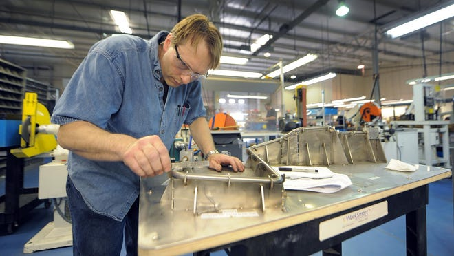 Rich Teffertiller works on tube for an airplane engine at L&E Engineering in Greenwood in 2013.