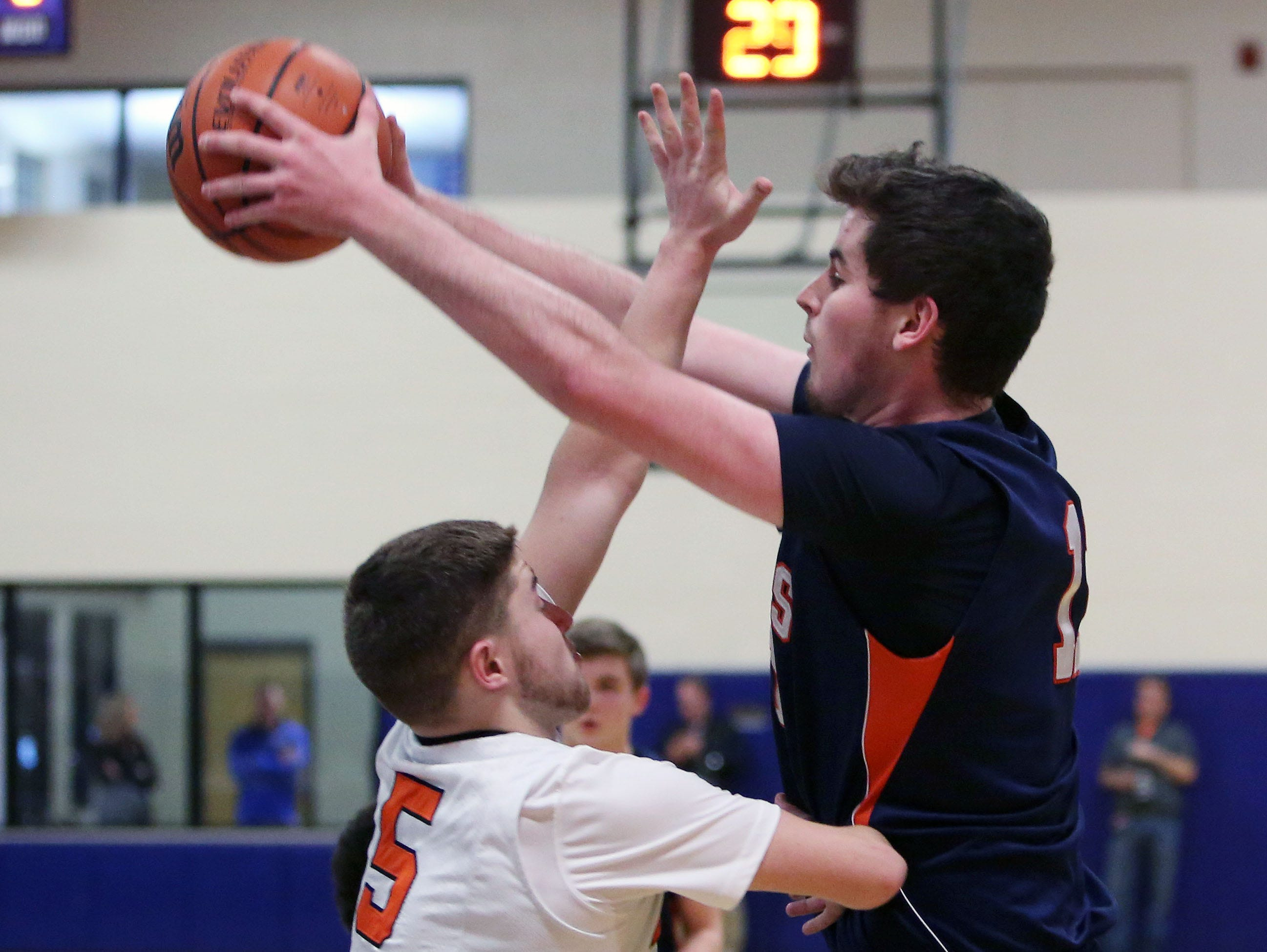 Briarcliff's Sean Crowley (11) has his path to the basket blocked by Marlboro's Nicholas Mongelli (5) during first half action in the boys basketball regional semifinal at Mount Saint Mary College in Newburgh March 2, 2016. Marlboro won the game 57-49.