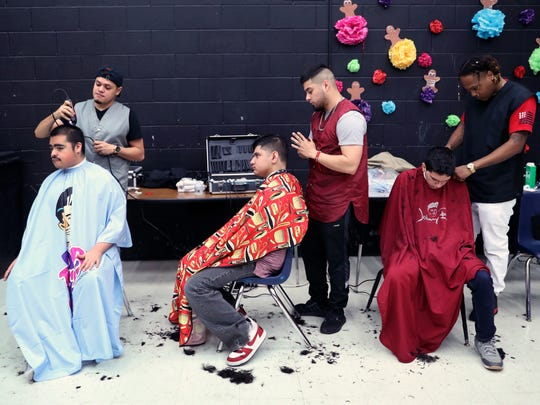Moody High School students William Rosas, 18 (from left), Joe Azocar, 16, and Erik Fuentes, 17, get their hair cut by barbers with the Chop Shop Anthony Trevino (from left), Alejandro Coruejo and Michael Cloud on Tuesday, Jan. 23, 2018, in preparation for the school's 15th annual Special Hearts Prom.