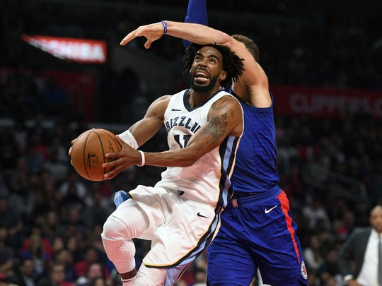 Memphis Grizzlies guard Mike Conley, left, is fouled