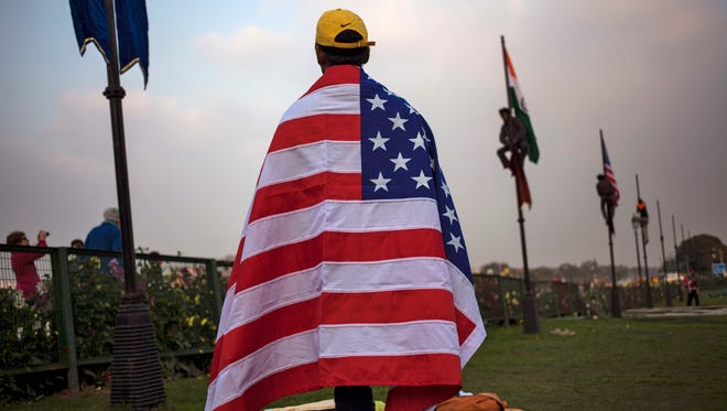 An Indian worker wears an American flag before it's hoisted up a flag pole in New Delhi, India.
