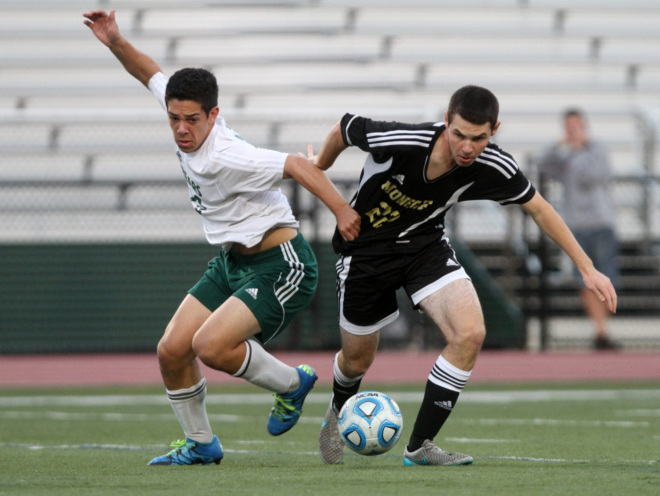 East Brunswick's Jason Kramer battles with Monroe's Ryan McCabe during the first half, Thursday, October 8, 2015, in East Brunswick, NJ.