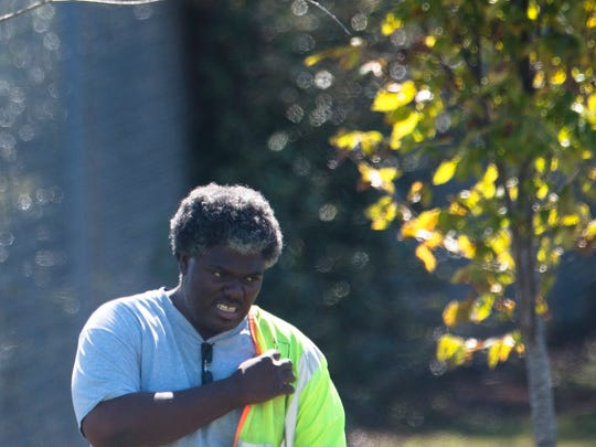 An ALDOT employee takes off his vest at an accident scene where three ALDOT employees where hit by a car on Tuesday, Oct. 31 2017, in Montgomery, Ala.