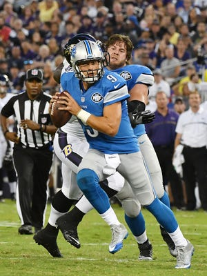 Lions quarterback Matthew Stafford takes off running as tackle Riley Reiff gets his helmet knocked off in the second quarter.