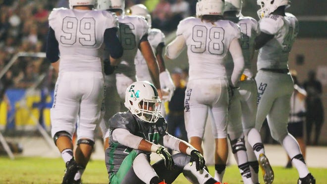 Fort Myers' Pierre Chery rests for a moment after being tackled for a loss against Naples on Friday.