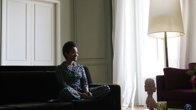 American content creator Tamu McPherson sits on the sofa at her home in Milan, Italy.