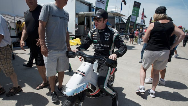 Simon Pagenaud scoots around the paddock area before qualifying.
