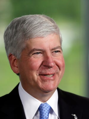 Gov. Rick Snyder smiles during an interview before signing legislation to provide state funding for Detroit municipal pensions as part of the city's bankruptcy process during a ceremony at the refurbished Globe Building in Detroit, Friday, June 20, 2014.