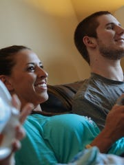 Chris Norton plays Wii with his fiancee Emily Summers and their future adopted daughter, Whittley Marquez, in their Michigan apartment. Emily struggled with depression and anxiety during this period of the couple's engagement.
