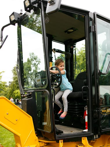 Avery Arana, 7, looks at her brother Ethan as they check out a road grader at Salem Public Works Day on Thursday, June 21, 2018, at Riverfront Park. Police, fire and other city employees were on hand to display and demonstrate city equipment in action.