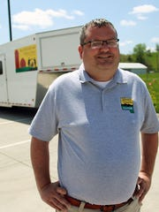 Johnson County Auditor Travis Weipert is considering a 2018 campaign for Iowa Secretary of State. In this 2014 file photo, he poses outside the county's votemobile at the Johnson County Fairgrounds.