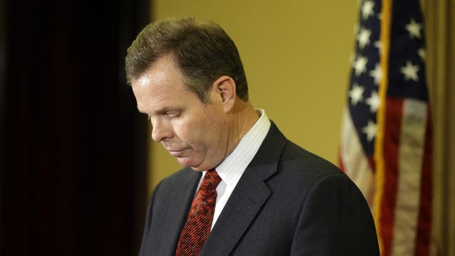 FILE - In this Nov. 21, 2013, file photo, Utah Attorney General John Swallow looks down during a news conference announcing his stepping down as Utah Attorney General. Prosecutors have filed a new money laundering charge against Swallow. Court records show that prosecutors also dropped a charge against Swallow on Wednesday, leaving the number of counts against him at 14. (AP Photo/Rick Bowmer, file)