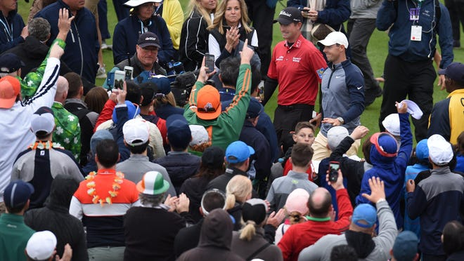 Players Championship 2019 winner Rory McIlroy is escorted to the trophy ceremony by the previous year's winner, Webb Simpson. Both are back in the field for this year's tournament.