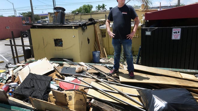 General Manager David Hazen stands on a dumpster of debris from the fire which heavily damaged H.G. Rooster's in West Palm Beach on June 26, 2020.  A fire broke out just after 2:30 a.m on May 19. Rooster's owner, A.J. Wasson, said he had lapsed on paying liability insurance for the building in order to keep paying his employees while the bar was closed due to coronavirus restrictions. The fire was ruled accidental.