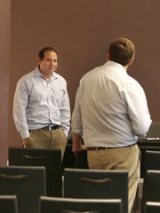 Alexander Kayne (left), general counsel for Omnicare, makes a motion to postpone and reconvene a shareholder's meeting until June 1 in a conference room of the Renaissance Hotel. John Kukulski (right) seconded the motion and it passed. None of the company officers were present.