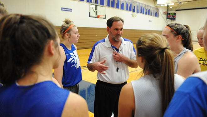 Livonia Ladywood varsity girls basketball players listen to new head coach Tom Bushart during a recent practice.