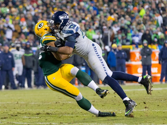 Dec 11, 2016; Green Bay, WI, USA; Seattle Seahawks linebacker K.J. Wright (50) commits a penalty while tackling Green Bay Packers tight end Richard Rodgers (82) during the third quarter at Lambeau Field. Green Bay won 38-10.  Mandatory Credit: Jeff Hanisch-USA TODAY Sports