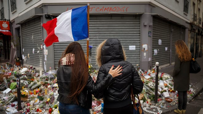 Two women stand outside the Petit Cambodge restaurant, a site of Friday's attacks in Paris.