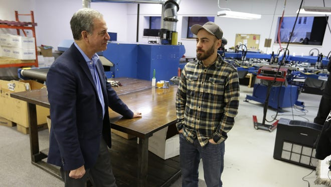 Russ Feingold talks with Offbeat Press owner Drew Mueske as Feingold toured the production area of the business Wednesday, Jan. 13, 2016, in Oshkosh. Feingold is touring all 72 Wisconsin counties getting a feel for the business climate around the state.