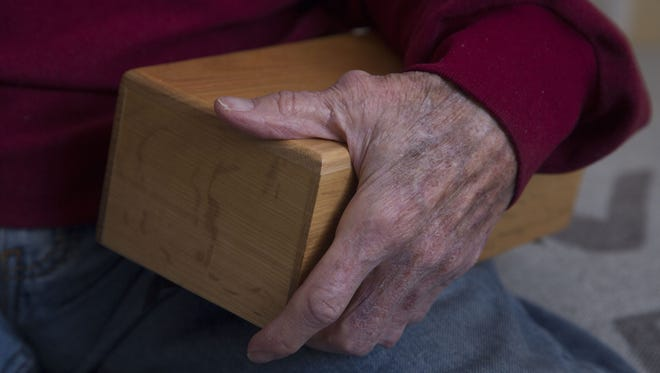 Jimmy Valentine holds a box that carries what he hopes are the remains of his wife, Mary Ann.