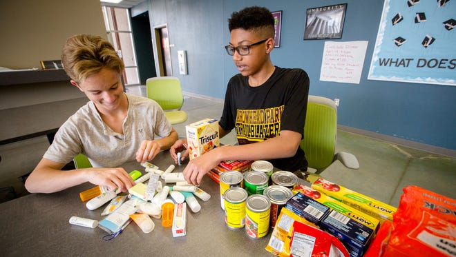 Ninth-graders Bryce Richards, 14, left, and Miles Davis, 15, pack a box of supplies for homeless teens as part of Project iCare at Arrowhead Park Early College High School.