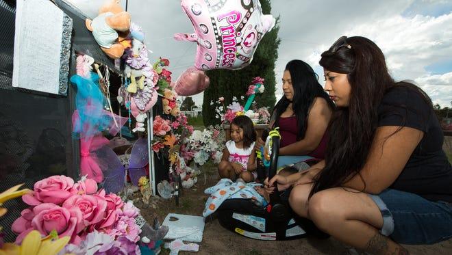 Doña Ana community residents Bryana Monsivaiz, right, Nikki Lucero, Zaiden Lopez, 5 months, and Kailyanna Martinez, 4, visit Brianna Mariah Lopez's grave on Wednesday, Sept. 21, 2016.