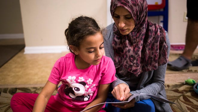 Mariam Shukri, 6, as a part of her homework, reads a book about bats to her mother, Mufida Ammar, on Thursday, February 2, 2017 in Clemson.