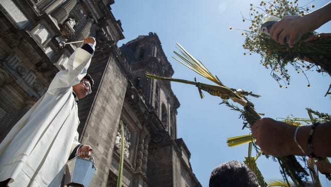 A priest blesses the palms held up by worshipers during Palm Sunday celebrations outside the Metropolitan Cathedral in Mexico City, on March 25, 2018.