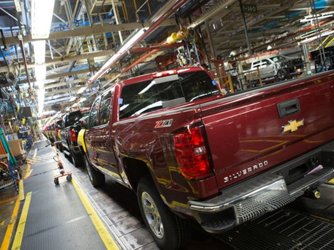 Nearly-complete Chevrolet Silverado pickup trucks are shown on a factory assembly line.