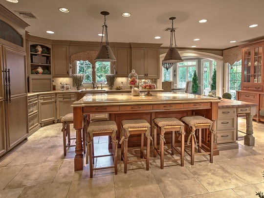 This kitchen features furniture-quality cabinets, a center island for dining and top-of-the-line appliances.