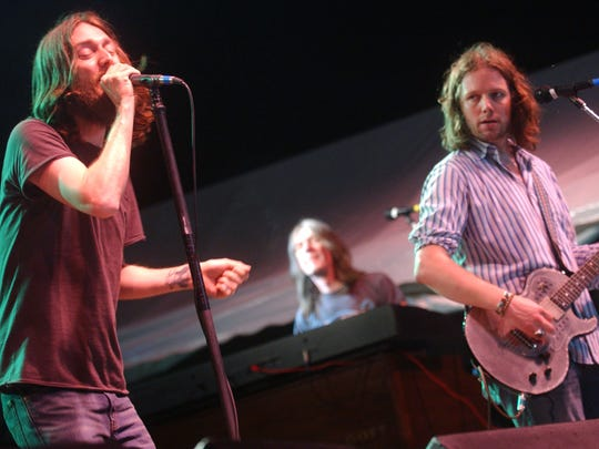 "Black Crowes lead singer Chris Robinson, left, belts out ""Jealous Again,"" while his brother, Rich Robinson, plays lead guitar in this file photo."